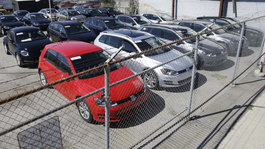 Volkswagen diesels are shown behind a security fence on a storage lot near a VW dealership in Salt Lake City. The carmaker is reeling from a scandal over its use of devices to fool emissions tests of diesel models.