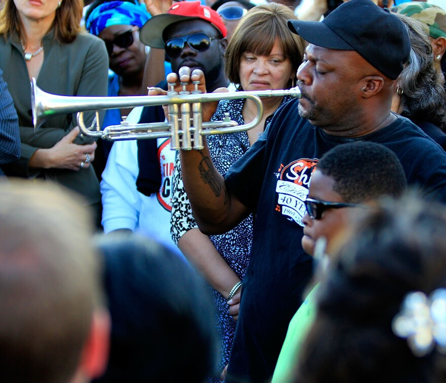 Kenneth Terry with the Treme Brass Band plays the trumpet Monday during a community response to a shooting during a Mother's Day parade in New Orleans.