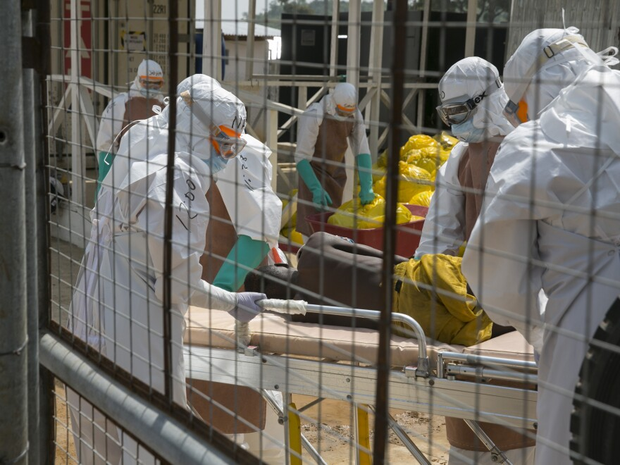 British health workers lift a newly admitted Ebola patient onto a wheeled stretcher in to the Kerry town Ebola treatment center outside Freetown, Sierra Leone, earlier this week.