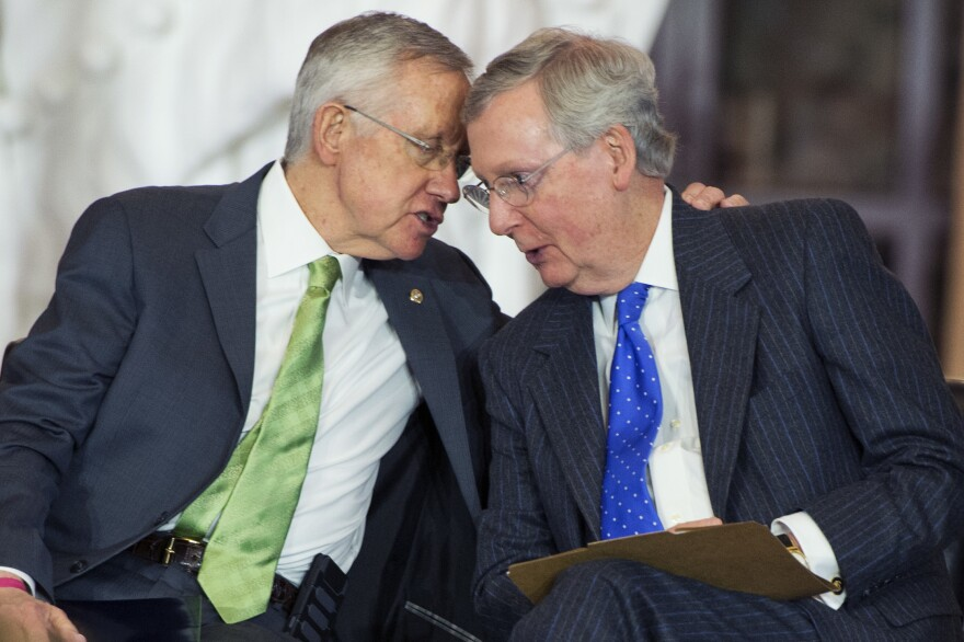 Sen. Harry Reid, then Democratic majority leader, left, speaks with GOP leader Mitch McConnell in 2014. They sparred in the Senate, and many point to their leadership for an increase in partisanship.
