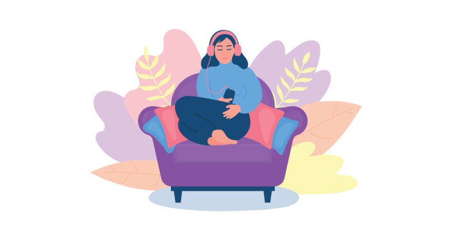 Image of a person sitting on a couch listening to headphones.