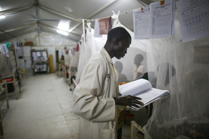 Late-night checkup: A South Sudanese nurse reviews a patient's chart.