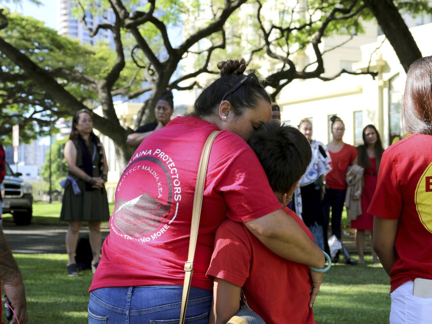 Joanna Pokipala and her son Kala Pokipala embrace while gathered with telescope protesters outside the Hawaii Supreme Court building in Honolulu in June.