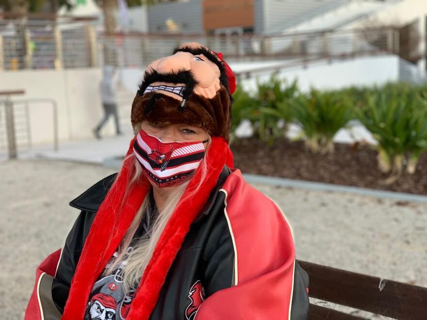 Woman sits on a bench in Tampa Bay Buccaneers attire.