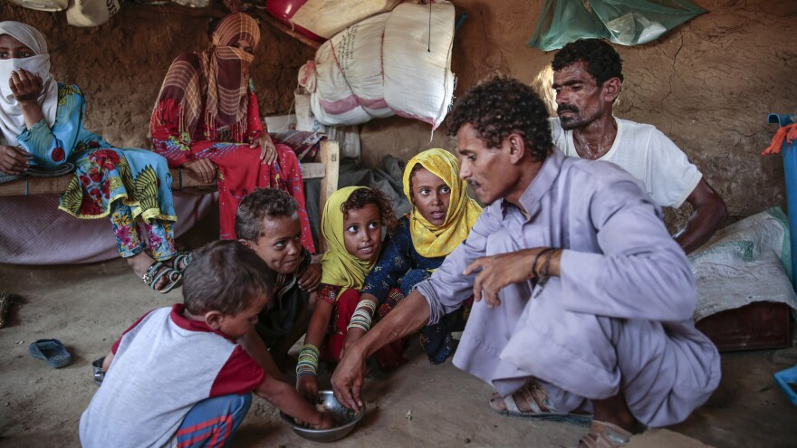 A man feeds children a paste made of green leaves, in Aslam, Yemen, northwest of the capital Sanaa. It's traditionally a side dish, but with the country facing extreme food shortages, it has become the main meal for some.