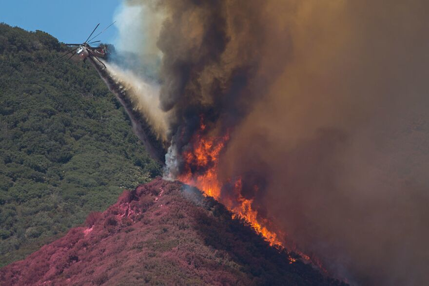 A firefighting helicopter pilot tries to stop flames close to jumping a ridge above Cajon Boulevard at the Blue Cut Fire on Thursday near Wrightwood, California.