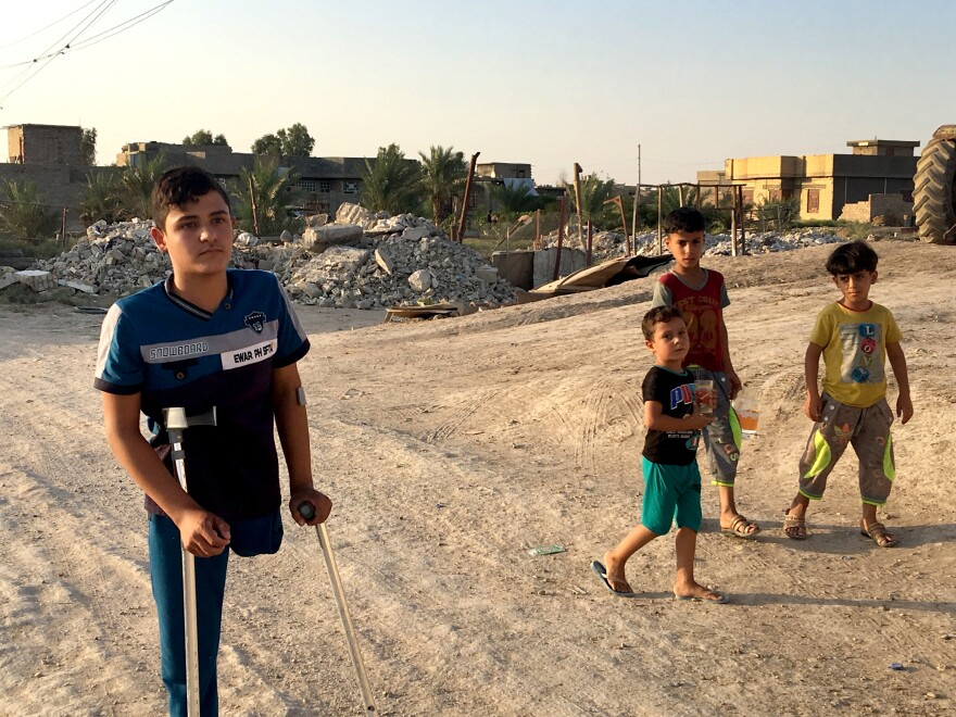 Mustafa Ahmed walks near home on the outskirts of Fallujah. As a baby, he was severely injured during the battle to liberate Fallujah from al-Qaida. His leg was amputated and he later received medical treatment in Portland, Oregon.