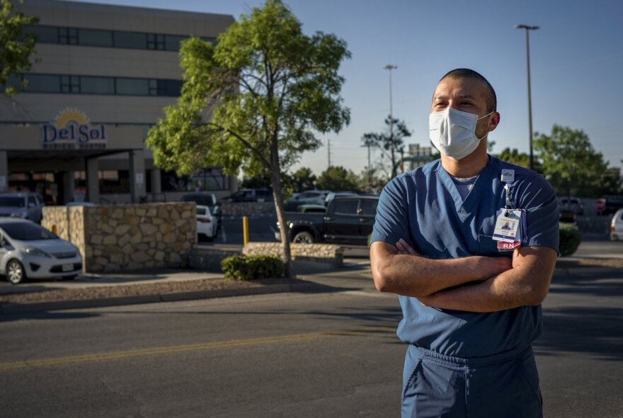 Josue Tayub in front of the hospital in scrubs and a mask.