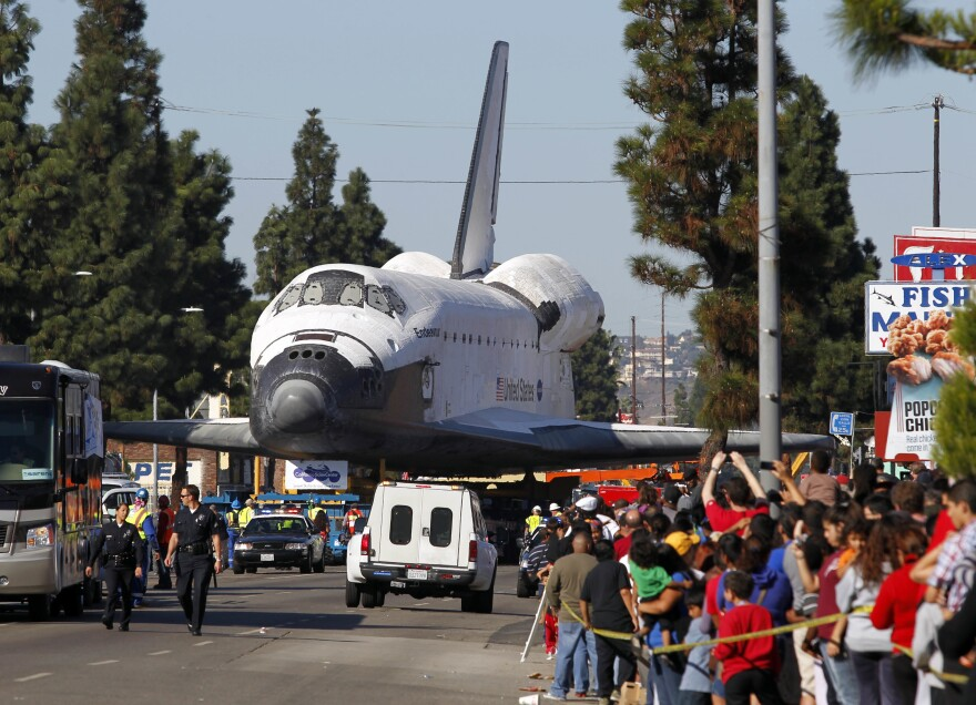 Fans watch the Space Shuttle Endeavour slowly move down Martin Luther King Blvd. in Los Angeles in 2012.