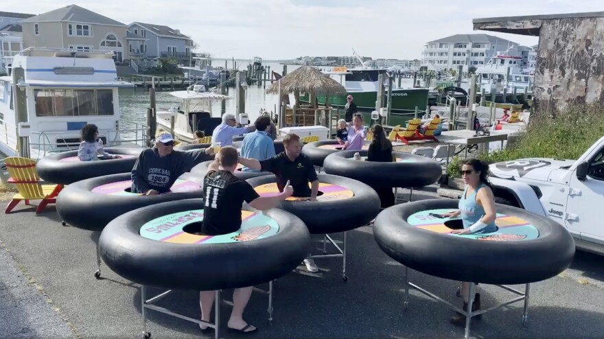 "Fish Tales Bar & Grill, a restaurant in Ocean City, Md., tries out ""bumper tables."" Designed by an event production company, they're meant to allow diners to practice social distancing."