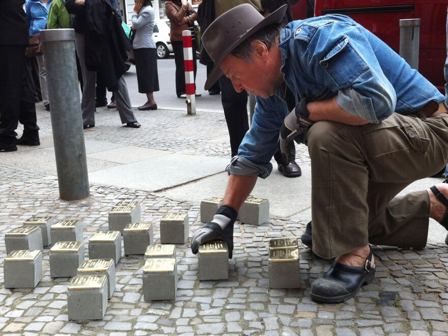 """Guenther Demnig is the artist and sculptor behind the stumbling stones. Here, he installs new bricks in Berlin. He says formal memorials are too abstract. Not so with the stumbling stones. """"Suddenly they are there, right outside your front door, at your feet, in front of you,"""" he says."""