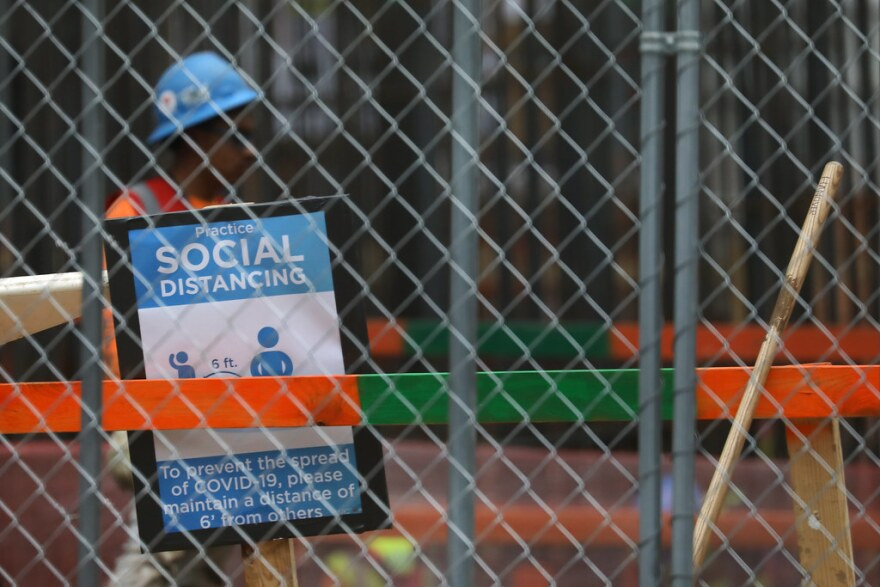 A construction worker stands near a sign about social distancing at a construction site.