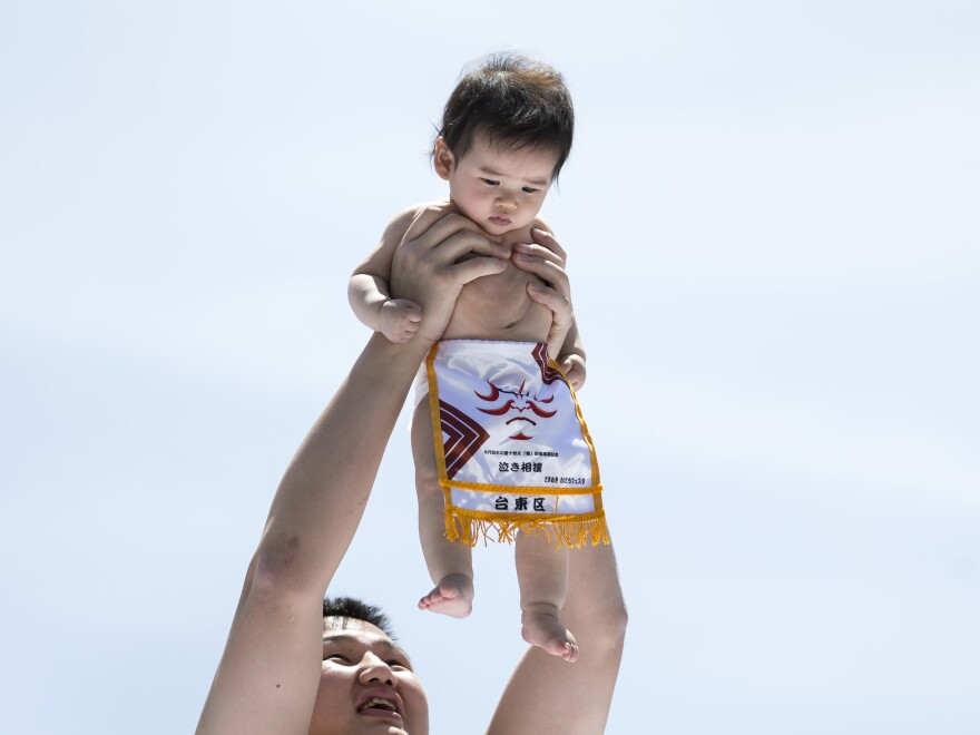 The number of babies born in Japan fell an estimated 5.9% this year, to under 900,000. Here, a baby is held aloft by a sumo wrestler during Tokyo's Nakizumo Festival in April.