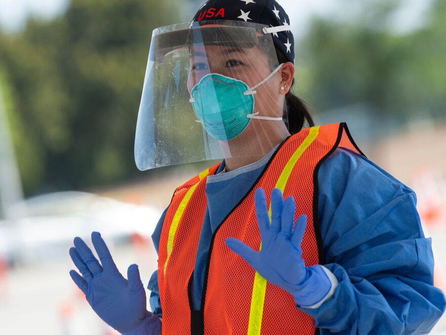 A health worker dons protective gear at a drive-through COVID-19 testing site set up by the Los Angeles Fire Department in Inglewood, Calif., on Monday.