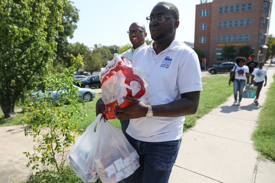 Gregory Gibson, Jr., President of the National Black MBA Association Austin Chapter, carries in items to be sorted for welcome baskets for evacuees from Hurricane Harvey.