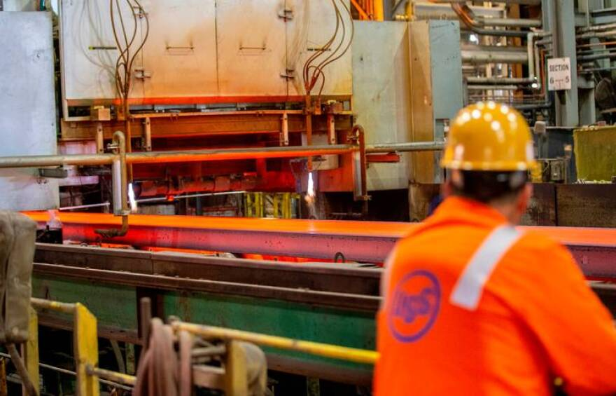 A U.S. Steel worker watches as a slab of steel moves through the production process.