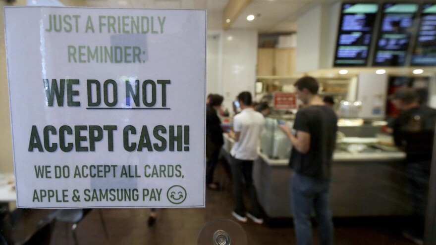A sign alerts customers that cash is not accepted at a shop in San Francisco last year. The city subsequently banned businesses from rejecting cash.