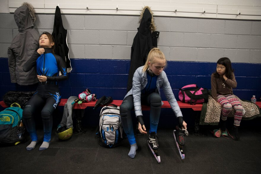 Kyubin Oh, 14, (left) Kamryn Lute, 13, and Ariel Chun, 7, get dressed for their 4:30 a.m. practice in Reston, Va., outside Washington, D.C.
