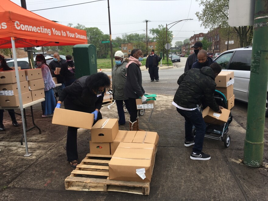 Residents of the Auburn-Gresham neighborhood line up for boxes of food at a weekly pop-up food pantry.