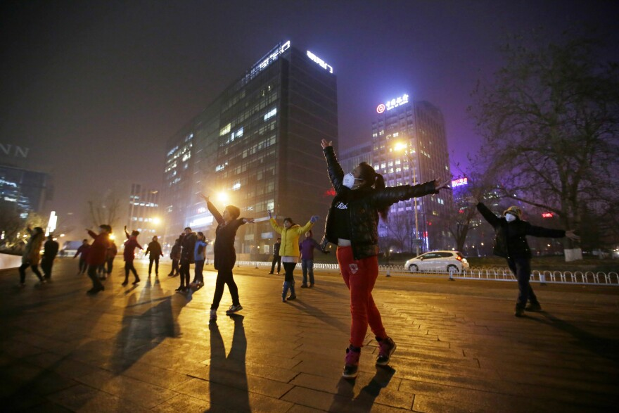 Women wearing masks and other residents dance during their daily exercise amid the heavy smog in Beijing on Monday.