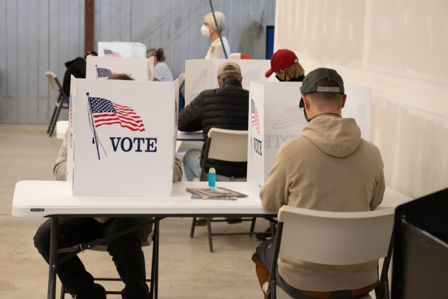 """A man in a ball cap and hoody, facing away from the camera, sits at a table enveloped by a cardboard privacy divider that says """"Vote"""" next to an American flag."""