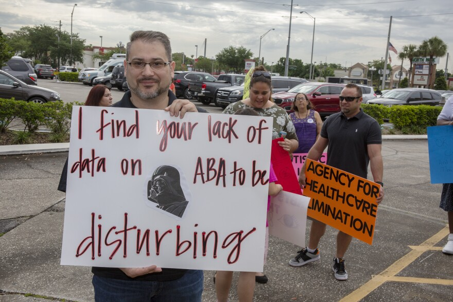 A man holds a sign that says I find your lack fo data on ABA disturbing, alongside a photo of Darth Vader.