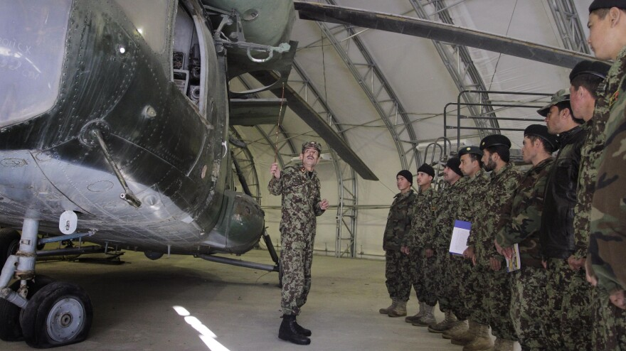 Afghan trainer Col. Din Mohammad, standing in front of a Soviet-made helicopter, speaks to new group of Afghan pilots and air crews at the Air Force University in Kabul on Jan. 16, 2012. The Afghan air force has only a small number of planes, pilots and spare parts and is attempting to ramp up training before the departure of U.S. and NATO forces.