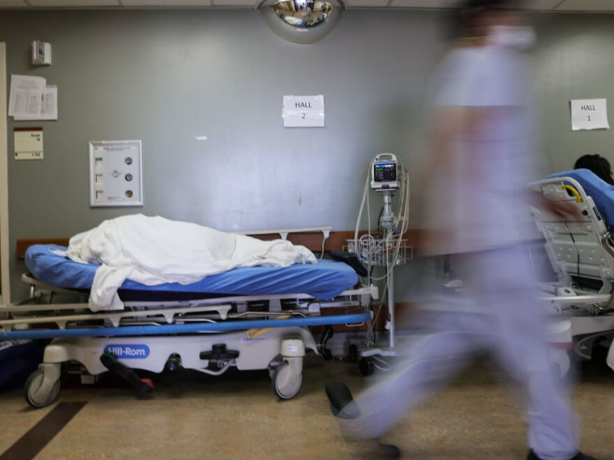 A patient lies on a stretcher in the hallway of the overloaded emergency room at Providence St. Mary Medical Center amid a surge in COVID-19 patients in Southern California in late December. Average new daily infections are now going down in California and much of the country.