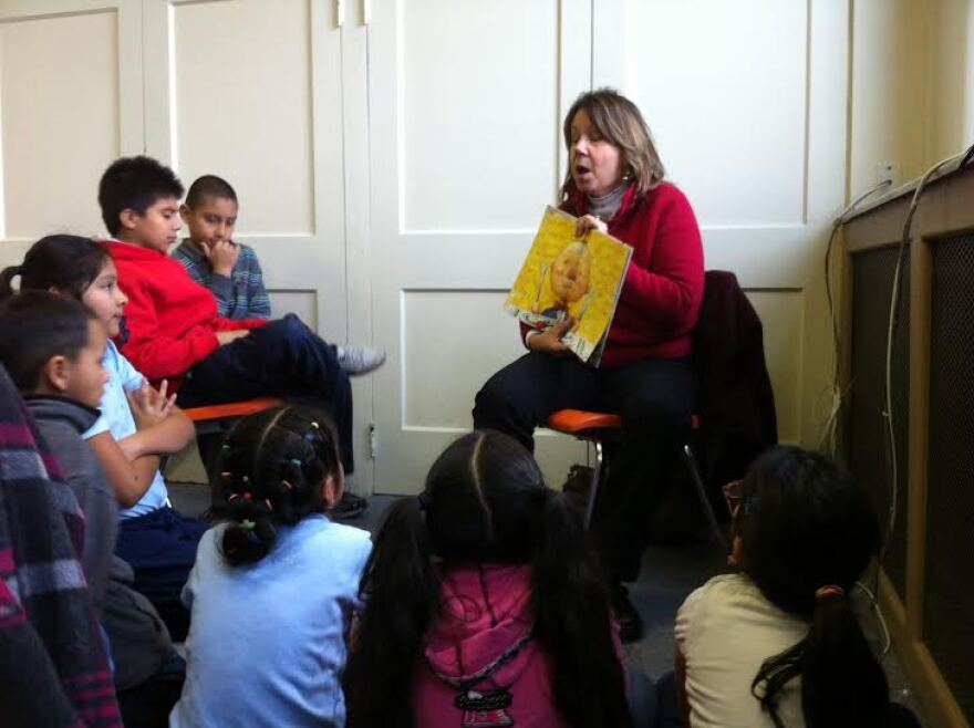 El Puente board member Richele O'Connor grabs students' attention with her spirited reading.