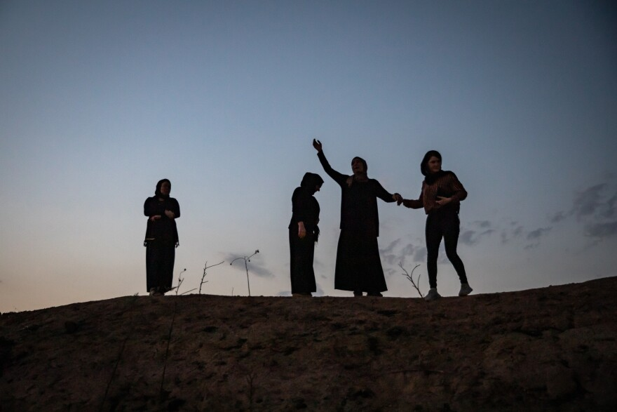 Former residents of the Yazidi village of Kocho, northern Iraq, mourn at the locations of mass graves where their family members were killed by ISIS.