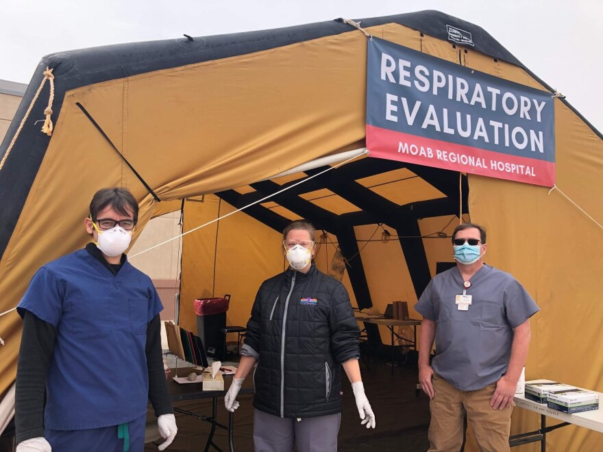 Photo of three people wearing face masks and standing in front of a tent