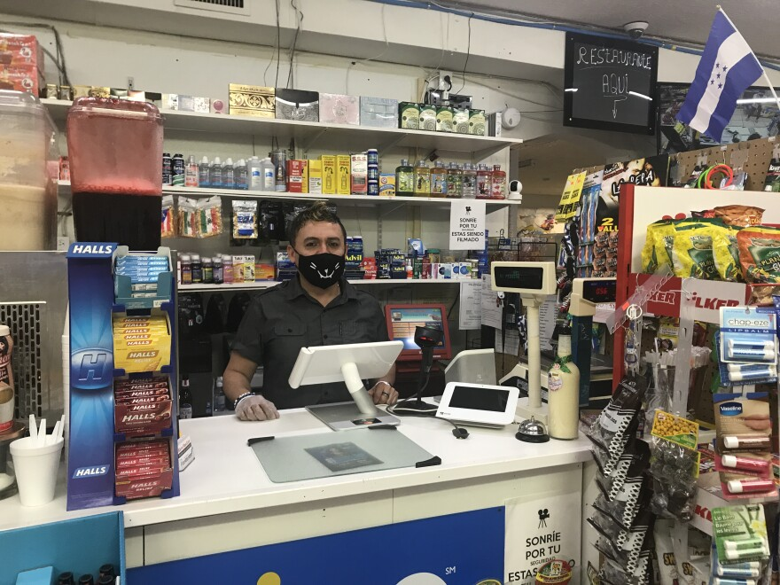 Fleming Lopez, owner of Mi Pequena Restaurant and Supermarket in Panama City, says he always wears a mask and gloves when interacting with customers on Sunday, Feb. 7, 2021.