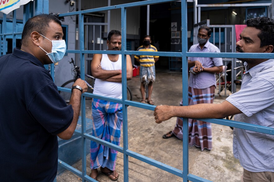 Singapore is seeing a spike in coronavirus cases among its hundreds of thousands of migrant workers. Above, a volunteer from a nonprofit group talks to migrant workers now confined to a factory that was converted to a dormitory as part of the effort to contain the spread of COVID-19.