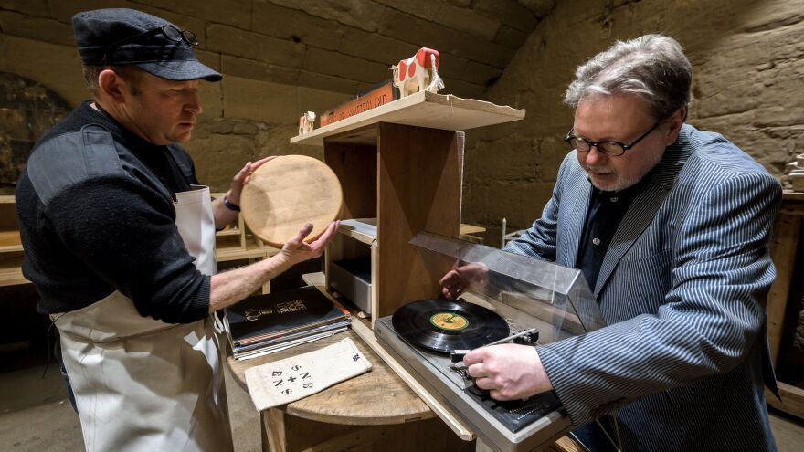 Swiss cheesemaker Beat Wampfler (left) and Michael Harenberg, director of the music department at the Bern University of the Arts, pose with a vinyl record and a wheel of Emmental.