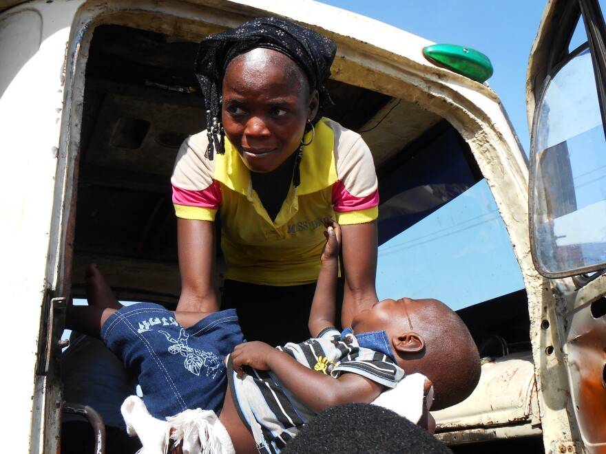 A woman who had fled to Yola to escape fighting in Mubi, at the border with Cameroon, lifts her son into the truck bound for Jos.