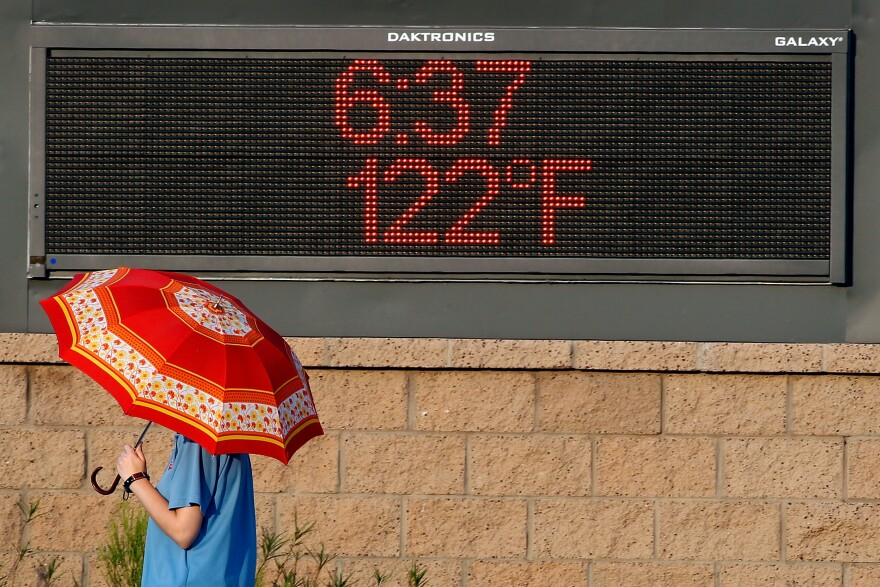 A pedestrian uses an umbrella to get some relief from the sun as they walk past a sign displaying the temperature on June 20, 2017 in Phoenix, Arizona. As 2020 comes to a close so does the hottest recorded decade.
