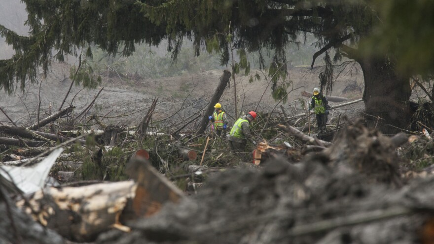 Crews work at the mudslide site Oso, Wash., Saturday, one week after a massive mudslide devastated a small community. Officials have dropped the number of missing people from 90 to 30.