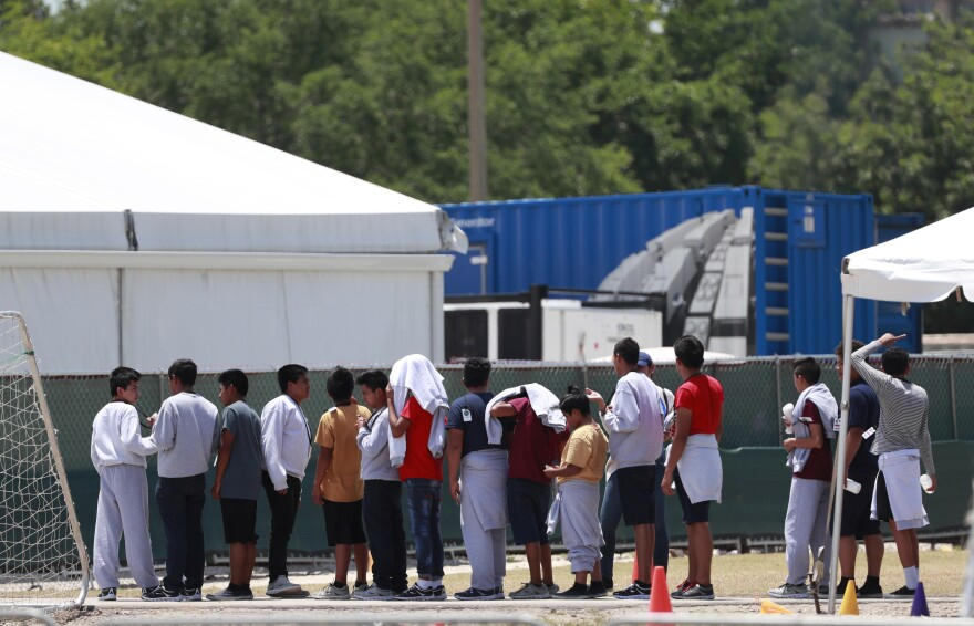 Migrant children line up outside a tent at the Homestead Temporary Shelter for Unaccompanied Children on Good Friday, Friday, April 19, 2019, in Homestead, Fla.