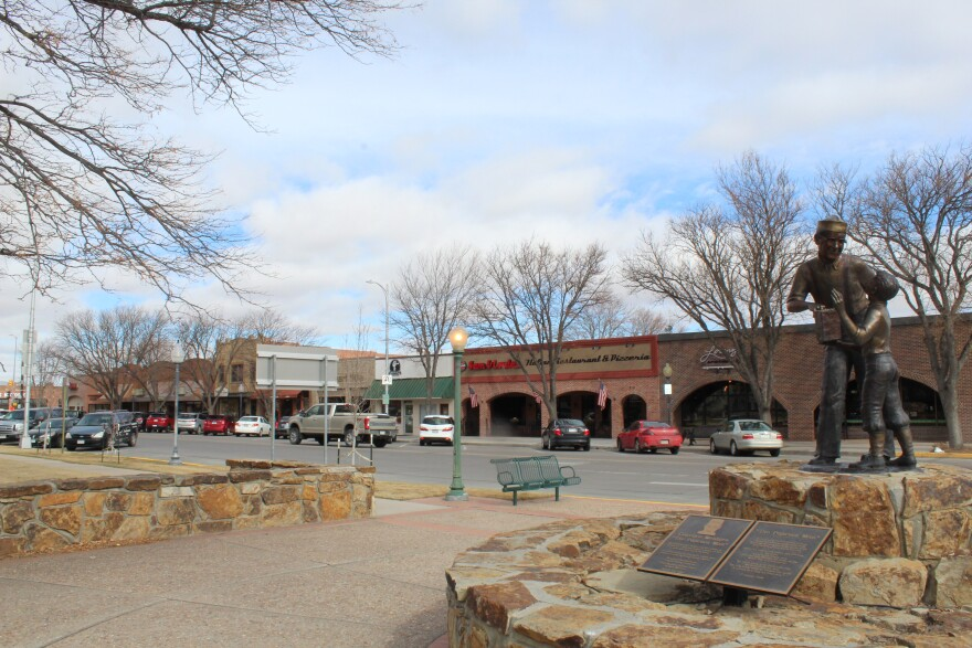 The main downtown strip of Sterling, Colorado. Taken from across the street, with a statue of a man giving a boy food in the foreground.