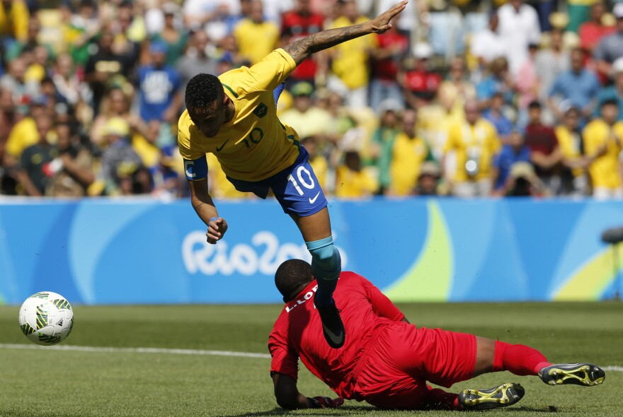 Brazil's Neymar soars over Honduras' goalkeeper Luis Lopez as he scores just 15 seconds into their semifinal game on Wednesday in Rio's Maracana Stadium. Brazil won 6-0 to advance to the gold medal game on Saturday against Germany — the team that knocked Brazil out of the 2014 World Cup with a lopsided victory.