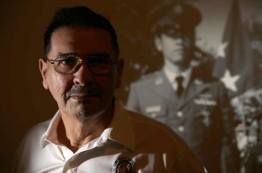 Santiago Erevia is one of only three living soldiers receiving a Medal of Honor on March 18. Behind him is a photo projection of his younger self in uniform.