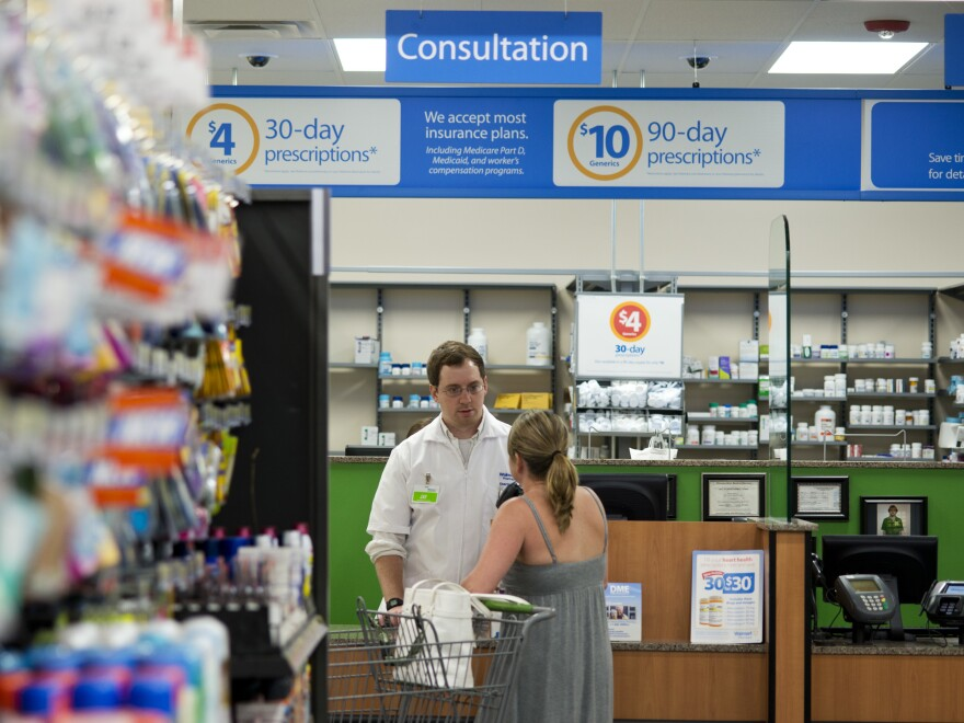 A pharmacist speaks with a customer at Walmart Neighborhood Market in Bentonville, Ark., in 2014. On Monday Walmart introduced a new set of guidelines for dispensing opioid medications.
