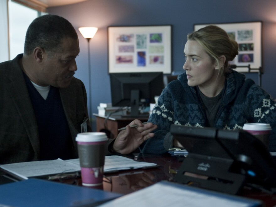 Laurence Fishburne as Dr. Ellis Cheever and Kate Winslet as Dr. Erin Mears in the thriller Contagion. Winslet's character was modeled on CDC epidemiologist Dr. Anne Schuchat.