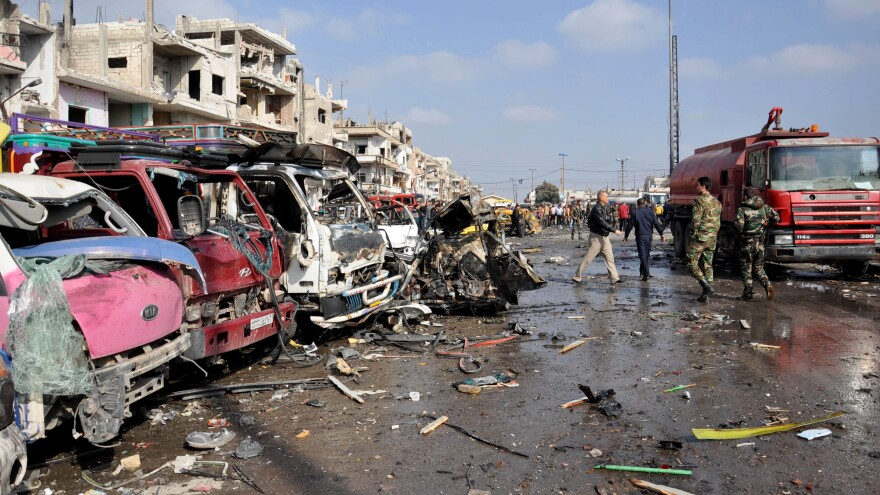 Damaged vehicles are seen at the site of a double car bomb attack in the Zahraa neighborhood of Homs in central Syria. The city is almost completely controlled by the Syrian government, and has regularly been targeted by attacks.