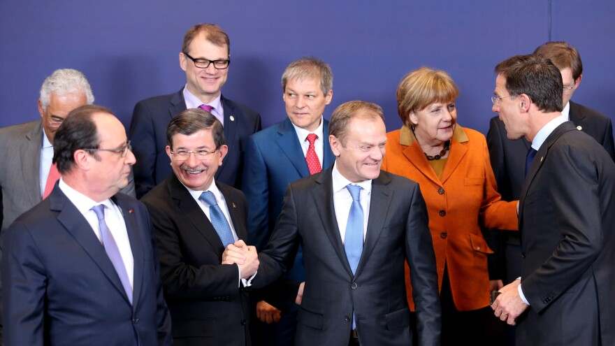 European Council President Donald Tusk (front center) shakes hands with Turkish Prime Minister Ahmet Davutoglu (front row, second from left) during a group photo at an EU summit Monday in Brussels.