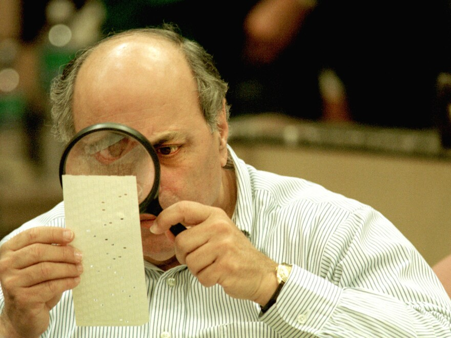 Judge Robert Rosenberg of the Broward County Canvassing Board uses a magnifying glass to examine a dimpled chad on a punch card ballot on November 24, 2000 during a vote recount in Fort Lauderdale, Fla.