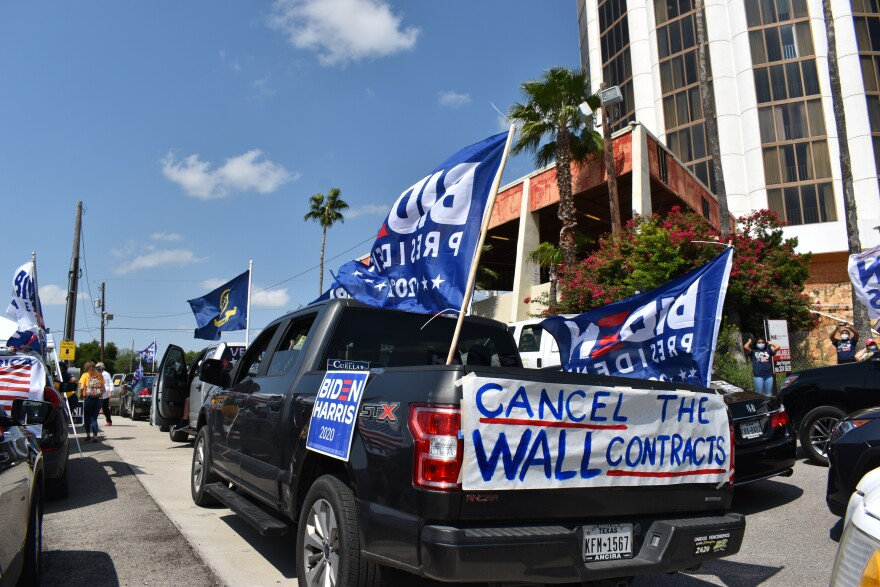 Cars drive through Laredo, Texas, in support of Joe Biden's presidential campaign in October 2020. Several cars tout Biden flags, as well as signs protesting the border wall.
