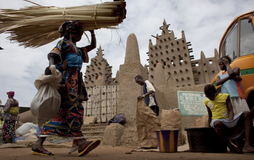 A woman walks by the Grand Mosque of Djenne on market day in Djenne, Mali, on Sept. 2. The UNESCO World Heritage-listed town is among the Malian tourist sites suffering from a huge drop in visitors after a coup took place in March and Islamist rebels seized control of the country's north.