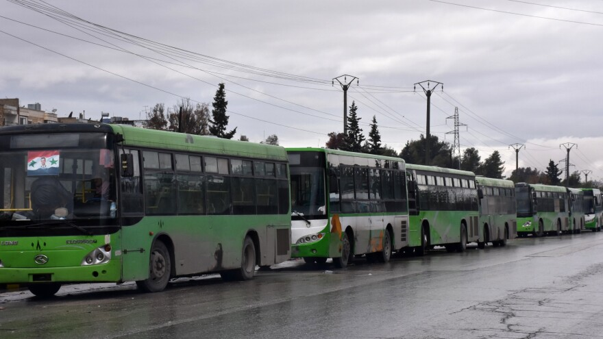 These buses — meant to evacuate civilians leaving from rebel-held areas of Aleppo — sit empty and waiting on Wednesday. Thousands of cold and hungry civilians crowded the streets of Aleppo uncertain of their future after their planned evacuation from the last rebel pocket of the city was delayed.