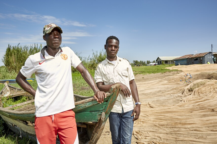 Brightone Otien (right) is 19 and a fellow fisherman at Nduru Beach. Brightone says he has been part of the <em>jaboya</em> practice — asking for sex before giving some of his catch to a woman fishmonger.